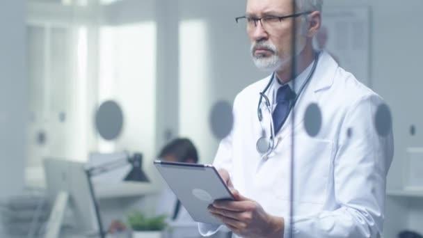 Oberarzt denkt über die Diagnose des Patienten nach und tippt auf einem Tablet-Computer. Sein Büro ist hell und modern.