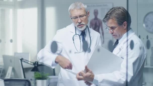 Zwei Fachärzte diskutieren das Patientenprotokoll. Beide sind Senior und erfahren. Ihr Büro wirkt modern und seriös.