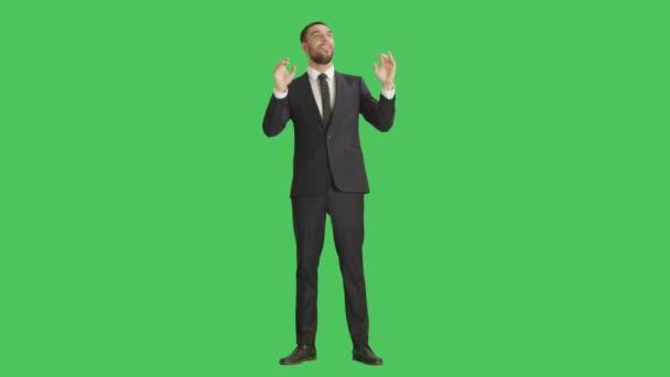 Dlouhý záběr na hezký usmívající se podnikatel zábavně se rozhlížel takže bít gesta. Zastřelen na pozadí zelená obrazovka