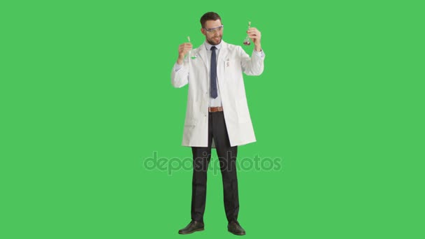 Long Shot of a Handsome Scientist Wearing Protective Glasses Mixing Liquids in a Beakers. Background is Green Screen.