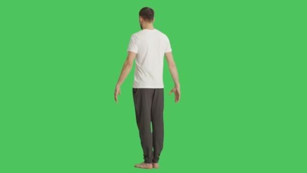 Dlouhý záběr na holé nohy muž na sobě tričko a tepláky a kamera se otočí kolem něj. Zastřelen na pozadí zelená obrazovka