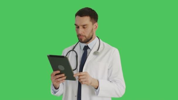Střední záběr usměvavý pohledný doktor dělá potáhněte prstem na tabletovém počítači gesta. Pozadí je zelená obrazovka.