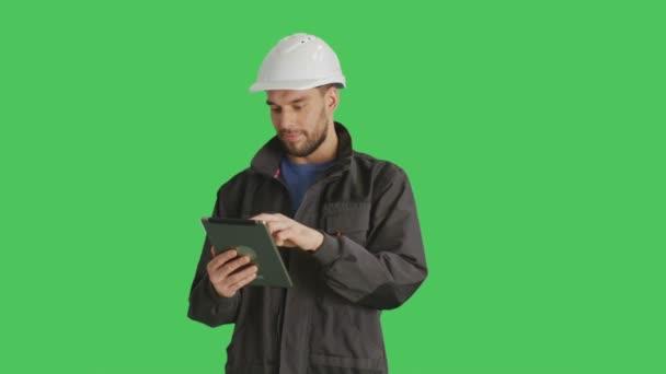 Colpo di metà di un bello lavoratore indossa bianco Hard Hat utilizzando Tablet Computer rendendo strisciata gesti su di esso. Girato su sfondo verde