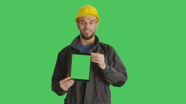 Střední záběr usmívající se práce s přilbou na držení svisle tabletový počítač s zeleným plátnem. Zelená obrazovka v pozadí.