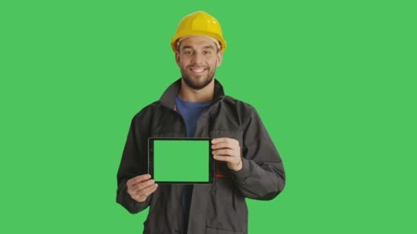 Die mittlere Einstellung eines lächelnden Arbeiters mit harter Mütze auf einem horizontal gehaltenen Tablet-Computer mit grünem Bildschirm. Green Screen im Hintergrund.