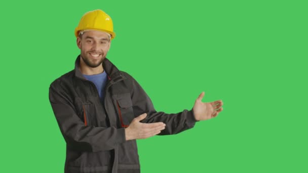 Mid Shot of a Smiling Worker Wearing Hard Hat Making Presenting Gestures. Background is Green Screen.