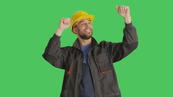 Die mittlere Einstellung zeigt einen Arbeiter, der einen Hut trägt, tanzt und die Hände hebt. Hintergrund ist Green Screen.