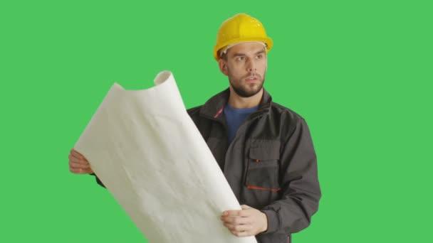 Střední pracovníka nošení čepice vypadá a plány a plány. Pozadí je zelená obrazovka.