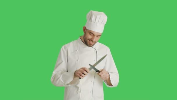 Střední záběr hezký usměvavý kuchař, zostření jeho nože. Pozadí je zelená obrazovka.