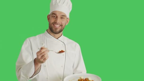Střední záběr hezký šéfkuchař plechovému držáku s Dish dekorační miska se lžičkou. Zastřelil se zelená obrazovka pozadí.
