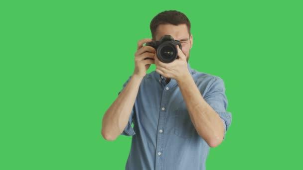 Mitte Schuss eines hübschen Fotografen fotografieren. Hintergrund ist Green Screen