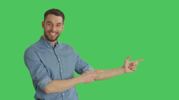 Střední záběr lhostejný člověk prst zbraň míří na produkt gesto. Pozadí je zelená obrazovka