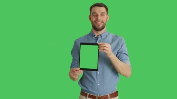 Střední záběr usmívajícího se muže na prezentaci svisle tabletový počítač s zeleným plátnem. Zelená obrazovka v pozadí