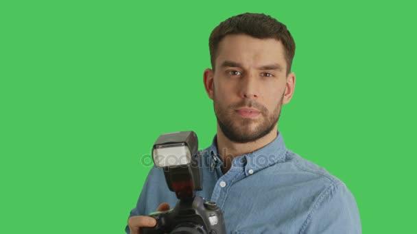Střední Detailní záběr hezký fotograf fotí se svým fotoaparátem. Střílel na zelené obrazovce