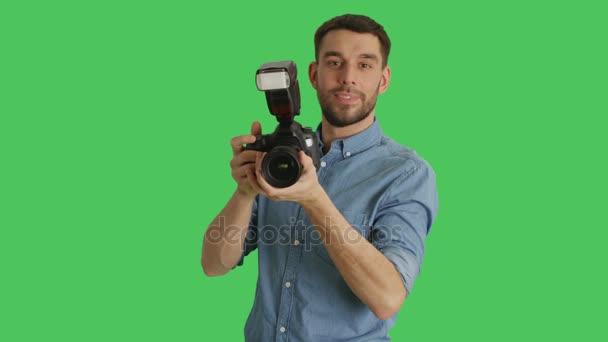 Střední záběr hezký fotograf fotí se svým fotoaparátem. Střílel na zelené obrazovce.