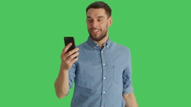 Střední stylové muže Video hovor a ukazující / směřující na památky za ním. Střílel na zeleném pozadí