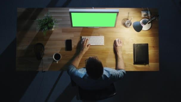 Pohled shora kreativní muži, kteří pracují na svůj stolní počítač s Mock-Up zelené obrazovky v noci. Tabulka světlo zapnuto.
