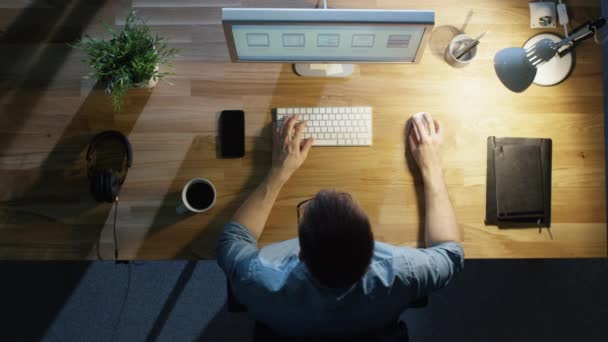 Pohled shora mladí kreativní návrháře pracovat na svém stolním počítači v noci. Pije kávu. Tabulka světlo zapnuto