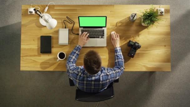Pohled shora mladý fotograf zpracování fotografií na jeho notebooku s Green Screen. Kamery, externí pevný disk a Notebook leží vedle něho