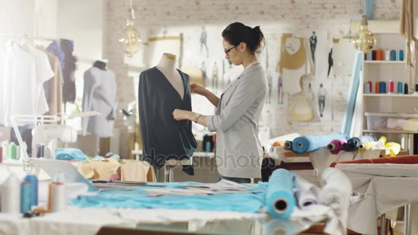 Krásná žena módní návrhář pracující s krejčovství manekýn, úprava halenku. Její Studio je Bright a Sunny, panáky postávají, visící oblečení, barevné tkaniny ležící na stole.