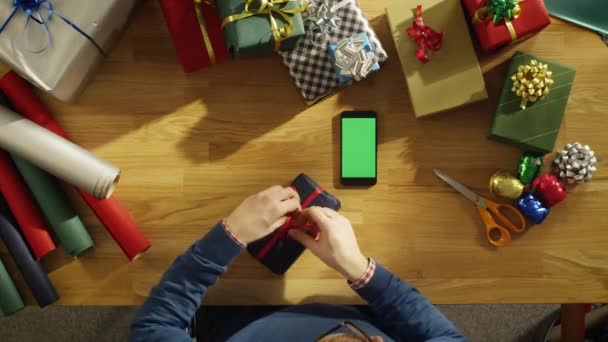 Top View of a Young Man Sitting at His Table Full of Packed Gifts Looking at Green Screened Smartphone. Warm Sunlight Covers His Table.