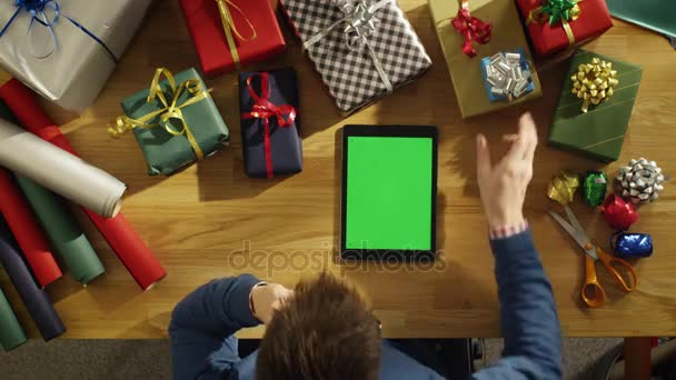 Top View of a Young Man Sitting at His Table Full of Packed Gifts Looking at Green Screened Tablet Computer. Warm Sunlight Covers His Table.