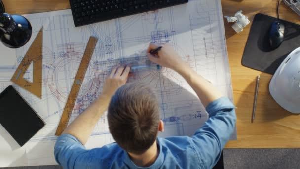 Pohled shora Technický inženýr pracuje na jeho plány na plány. Různé výkresu objekty ležící na jeho stole