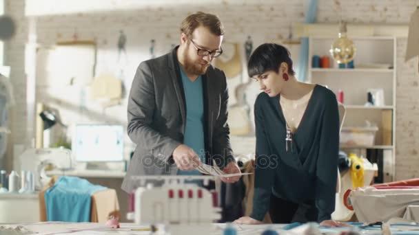Ženské a mužské módní návrhář výběrem skici pro jejich nové kolekce oblečení. Studio je slunečné. Barevné tkaniny, zavěšené oblečení a šitím položky jsou viditelné