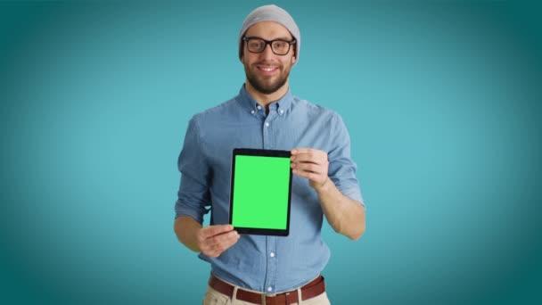 Střední záběr usmívajícího se muže módní prezentace nám tabletový počítač s izolované Mock-up zelená obrazovka. Zastřelen na Teal barevném pozadí