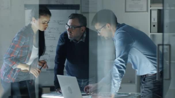 Am großen Konferenztisch arbeiten bis spät in die Nacht Konstrukteure an einem Projekt. Sie tauschen Meinungen aus und korrigieren Dokumente. Tisch ist beleuchtet. Schuss in Zeitlupe.