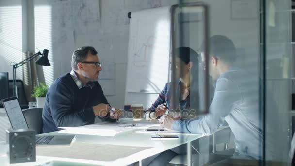 Tým inženýrů průmyslové sedí u skleněné konferenční stůl, o probíhajícím projektu. V tabulce vidíme, plány, dokumenty, prototypů součástí. V pozadí tabule a plány na stěnách.