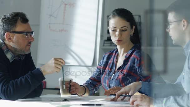Das Team der Wirtschaftsingenieure sitzt am gläsernen Konferenztisch und diskutiert das laufende Projekt. Auf dem Tisch liegen Entwürfe, Dokumente. im Hintergrund Whiteboard und Baupläne an Wänden.