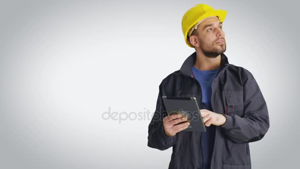 Mid Shot of a Worker in a  Hard Hat Holding Tablet Computer and Looking Around. Shot with White Background.