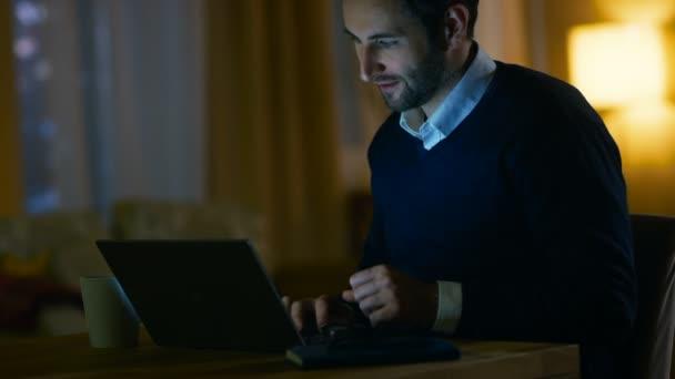 Středního věku muže u stolu, pracující na přenosném počítači. On je spokojený. On se jen usmívá. V pozadí jeho byt v žlutých tónů s výhledem na mrakodrapy.