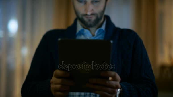 Portrait of a Man at Home Holding and Using Tablet Computer. Screen Illuminates Him. His Apartment is Done in Warm Yellow colours and Has Skyscraper View.