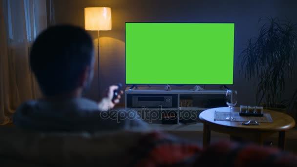 Este vissza kilátás egy középkorú idősebb ember ül egy kanapén tévénézés a nagy, lapos képernyős, távirányítóval csatornákat kapcsol. Az este