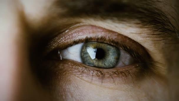 Nahaufnahme der Augen eines blinkenden Mannes. Es ist grau mit braunen Punkten. Schuss in kalten Farben.
