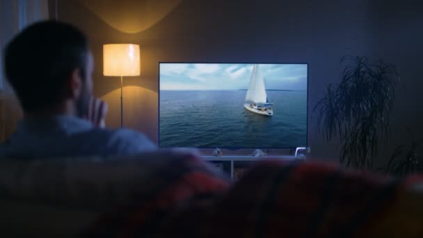 Back View of a Man Sitting on a Couch Watching Romantic Movie with Yachting and Camping in it on His Big Screen TV. Its Evening.