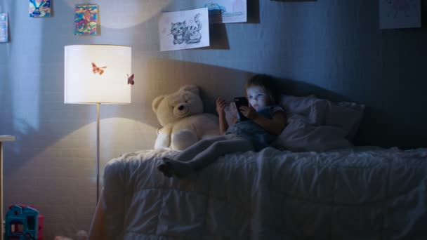 Cute Little Girl Lies on Her Bed and Watches Cartoons on a Smartphone. Her Floor Lamp is On.