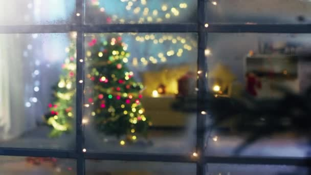 Beautiful Moving Shot From a Snowy Street Into the Window. Seeing Decorated Christmas Tree with Gifts Under It and Lots of Christmas Lights in the Room with cozy Celebratory Atmosphere.