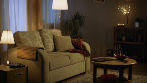 Dlouhý záběr obývacího pokoje ve večerních hodinách. Světla svítí, barvy jsou měkké a příjemné.