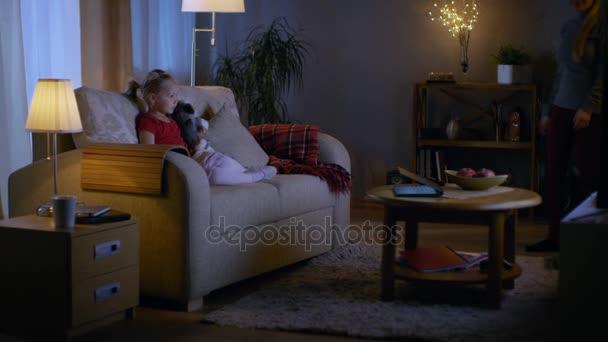 Este a kislány ül egy kanapé a nappaliban. Ő tartja őt puha játék és órák Tv, a szép anya jön-ban és csatlakozik rá egy kanapé.