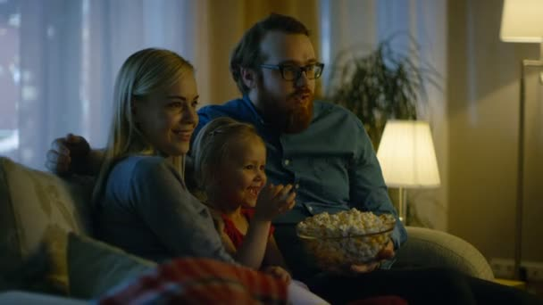 Apa, anya és a kislány tévénézés. A hangulatos nappaliban a kanapén ül, és pattogatott kukoricát enni. Az este.