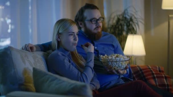 Pár figyel Tv. A hangulatos nappaliban a kanapén ül, és pattogatott kukoricát enni. Az este.