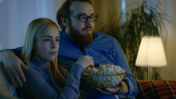 Barátja, a barátnője tévénézés. A hangulatos nappaliban a kanapén ül, és pattogatott kukoricát enni. Az este.