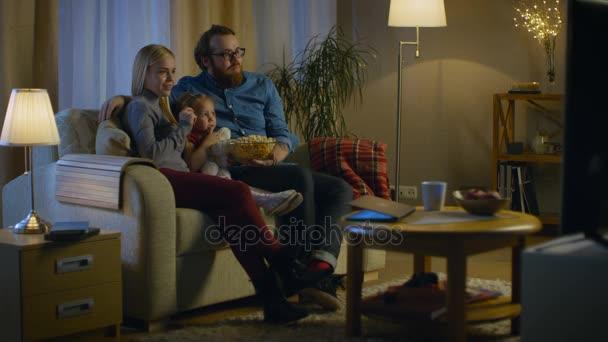 Hosszú lövés egy apa, anya és a kislány tévénézés. A hangulatos nappaliban a kanapén ül, és pattogatott kukoricát enni. Az este.