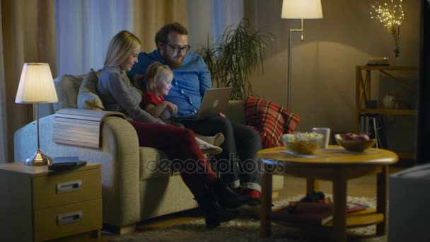 Hosszú lövés egy apa, anya és a kislány tévénézés. Ülnek a kanapén, a hangulatos nappaliban, apja tartja Laptop térdre. Az este.
