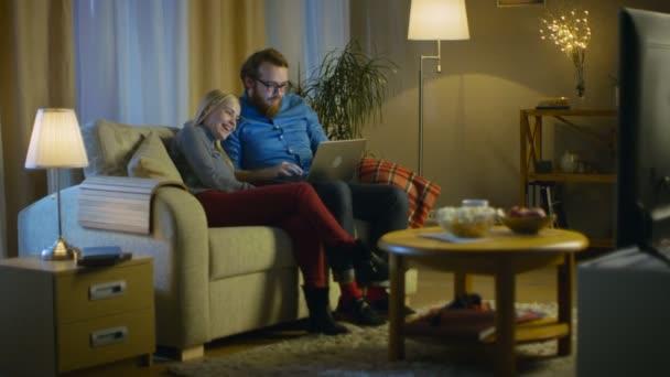Barátnője és barátja laptop térdre a kanapén ül, néz video- és a szórakozás. Nappali egy hangulatos. Az este.