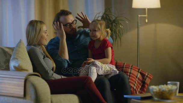 In the Evening Family Spends Time Together Sitting on a Couch in a Living Room. Little Girl Sits on Her Fathers Laps and Parents Tickle Her.