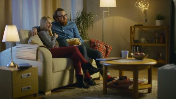 Az este férfi és a nő ül a kanapén tévénézés és étkezési Popcorn. Nappali egy hangulatos.